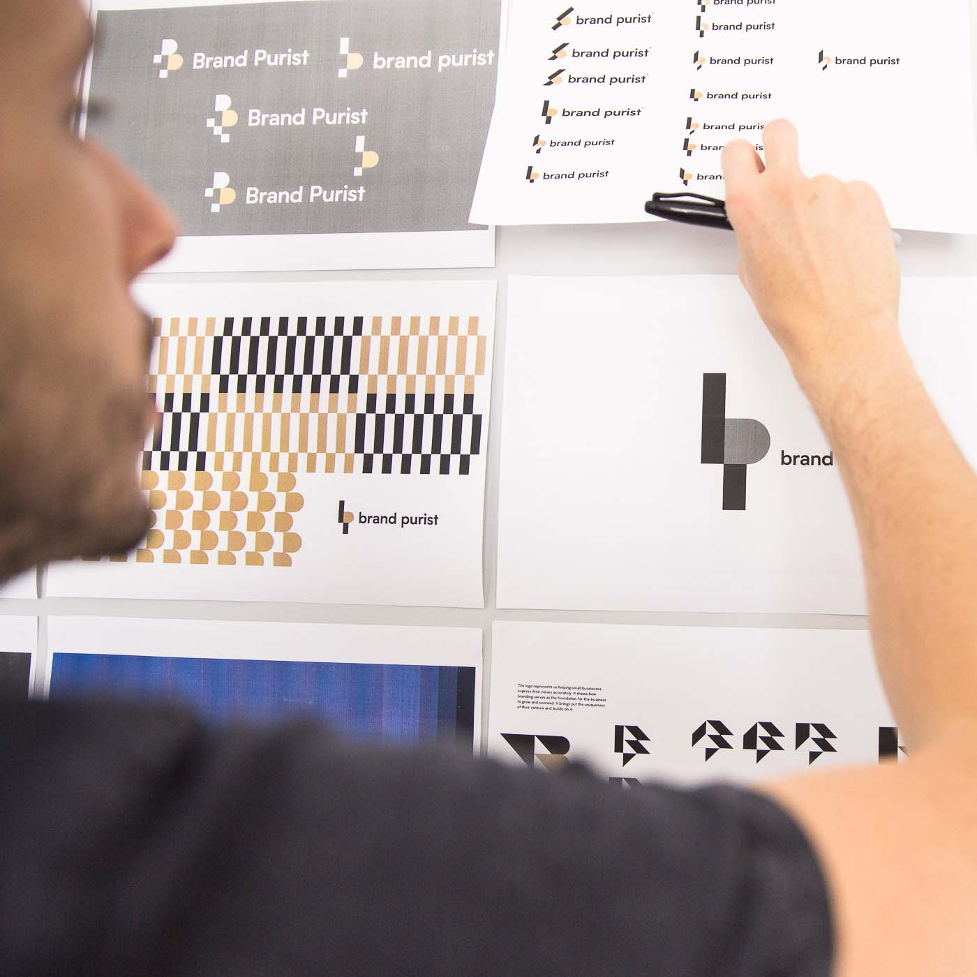 Designer is reviewing logo designs printed and stuck on a wall.