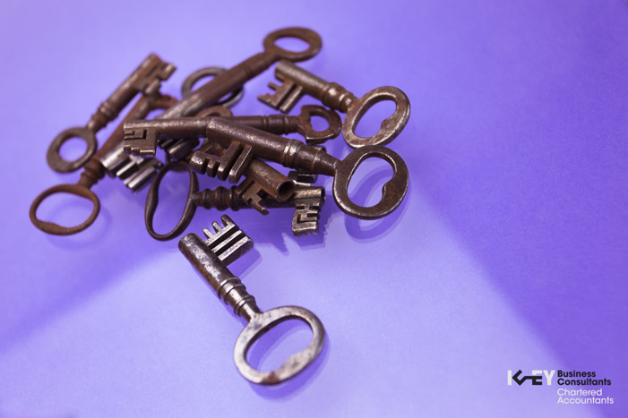 Rusty, old keys in a pile photographed on purple background.