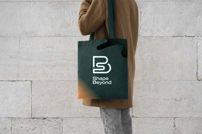 Photo of a tote bag with the Shape Beyond logo printed on it.