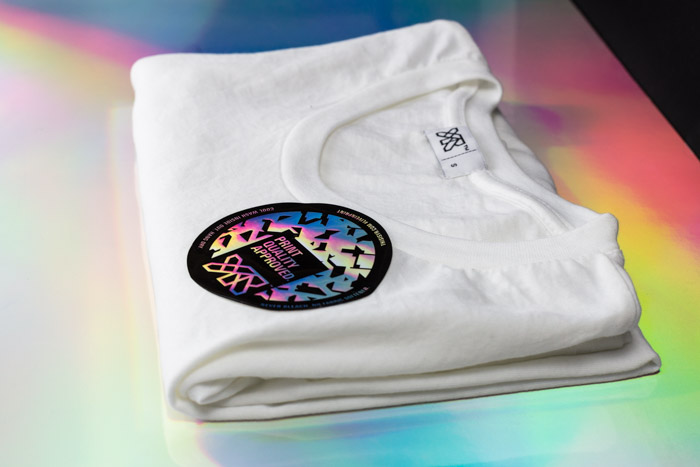 Close up of holographic sticker on a YR t-shirt.